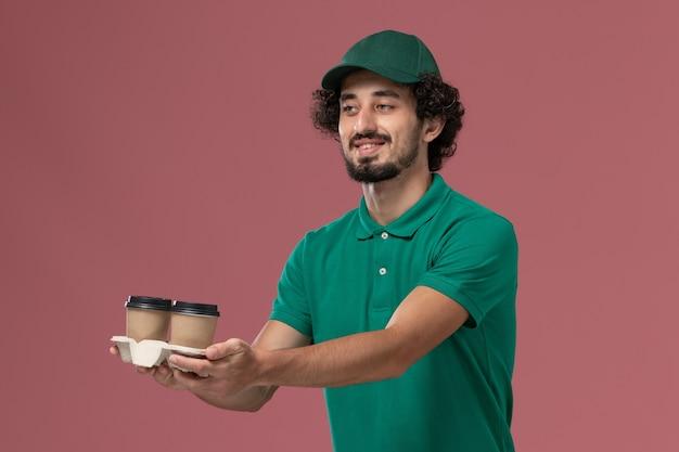Vooraanzicht mannelijke koerier in groen uniform en cape met koffiekopjes op de roze achtergrond uniforme levering dienst baan mannelijk bedrijf