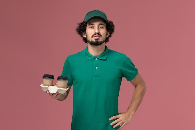 Vooraanzicht mannelijke koerier in groen uniform en cape met koffiekopjes op lichtroze achtergrond uniforme levering service werknemer baan