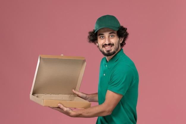 Vooraanzicht mannelijke koerier in groen uniform en cape met lege voedseldoos op roze achtergrond service werknemer uniforme levering werk man
