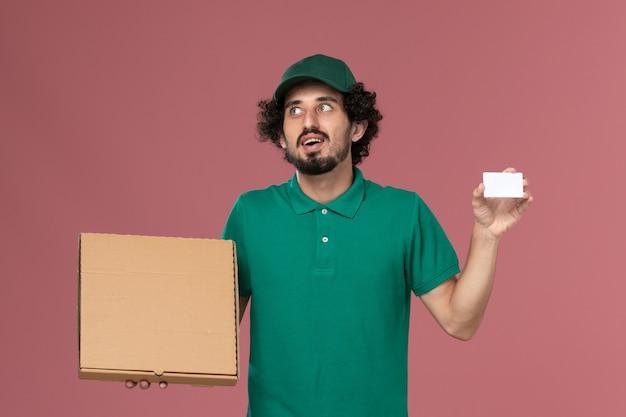 Vooraanzicht mannelijke koerier in groen uniform en cape met levering voedsel doos en kaart op de roze achtergrond service uniforme levering