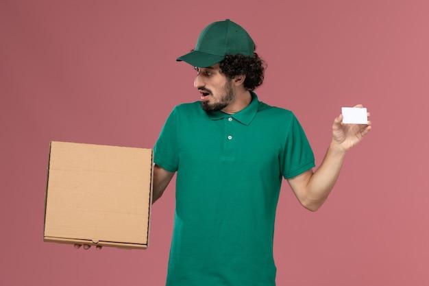 Vooraanzicht mannelijke koerier in groen uniform en cape met levering voedsel doos en kaart op roze vloer service uniforme levering baan werk