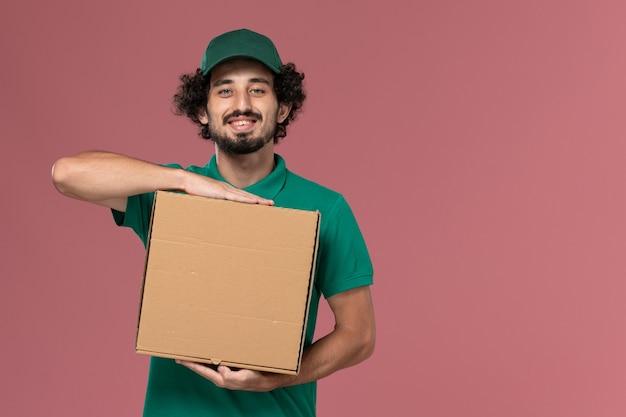 Vooraanzicht mannelijke koerier in groen uniform en cape met levering voedseldoos met glimlach op roze achtergrond service baan uniforme levering