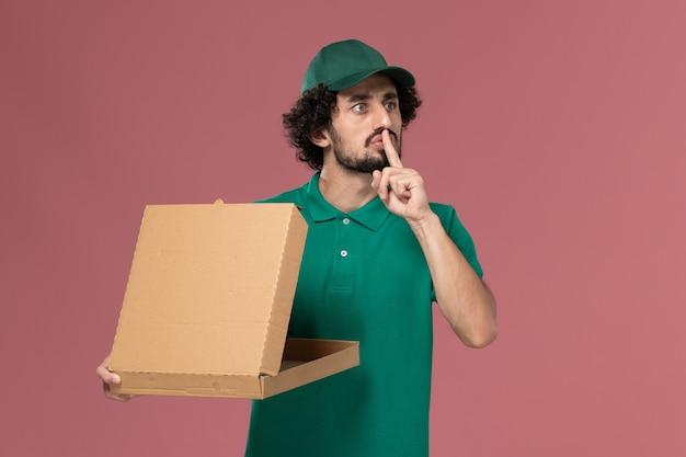 Vooraanzicht mannelijke koerier in groen uniform en cape met levering voedseldoos op roze achtergrond service werknemer uniforme levering