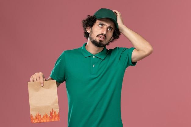 Vooraanzicht mannelijke koerier in groen uniform en cape met papier voedselpakket denken aan de roze achtergrond service werknemer uniforme levering baan