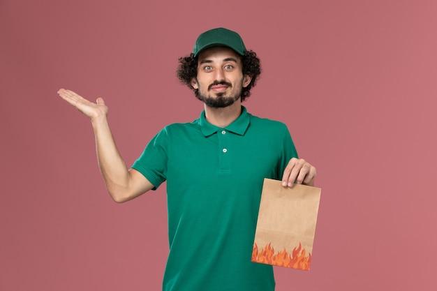 Vooraanzicht mannelijke koerier in groen uniform en cape met papier voedselpakket op roze achtergrond service werknemer uniforme levering baan