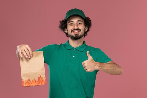 Vooraanzicht mannelijke koerier in groen uniform en cape met papieren voedselpakket met glimlach op de roze achtergrond service werknemer uniforme bezorgbaan