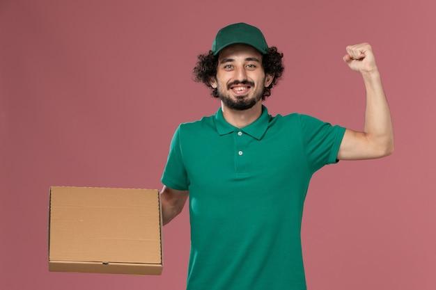 Vooraanzicht mannelijke koerier in groen uniform en cape met voedseldoos die zich verheugt op roze achtergrond service werknemer baan uniforme levering
