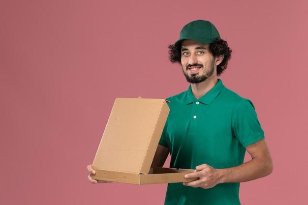 Vooraanzicht mannelijke koerier in groen uniform en cape met voedseldoos op roze achtergrond service werknemer uniforme levering werk man