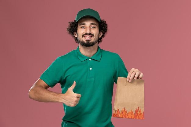 Vooraanzicht mannelijke koerier in groen uniform en cape met voedselpakket op roze achtergrond service uniforme levering baan werknemer mannetje