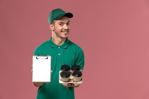 Vooraanzicht mannelijke koerier in groen uniform glimlachend en bruine koffiekopjes en blocnote op roze achtergrond te houden