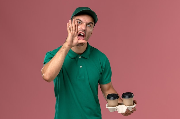 Vooraanzicht mannelijke koerier in groen uniform schreeuwen en bruine koffiekopjes op roze achtergrond te houden