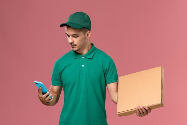 Vooraanzicht mannelijke koerier in groen uniform voedseldoos houden en met behulp van zijn telefoon op de roze achtergrond