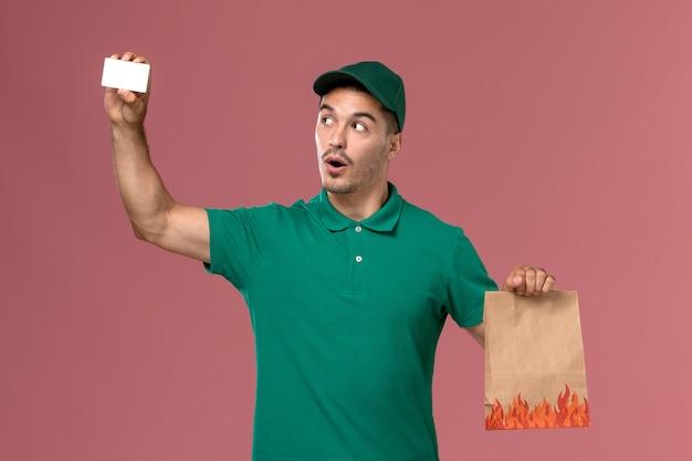 Vooraanzicht mannelijke koerier in groen uniform voedselpakket en kaart op het roze bureau te houden