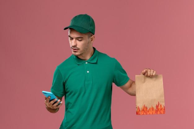 Vooraanzicht mannelijke koerier in groen uniform voedselpakket houden tijdens het gebruik van zijn telefoon op roze achtergrond
