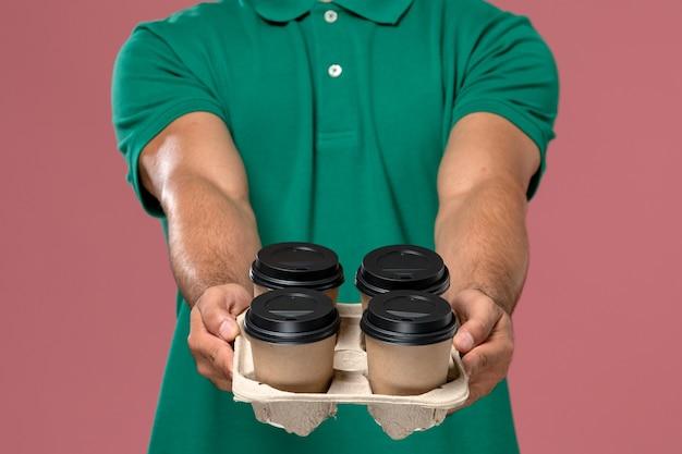 Vooraanzicht mannelijke koerier in groene uniform koffiekopjes op de roze te houden