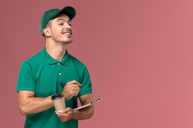 Vooraanzicht mannelijke koerier in groene uniforme koffiekop en blocnote schrijven op het lichtroze bureau