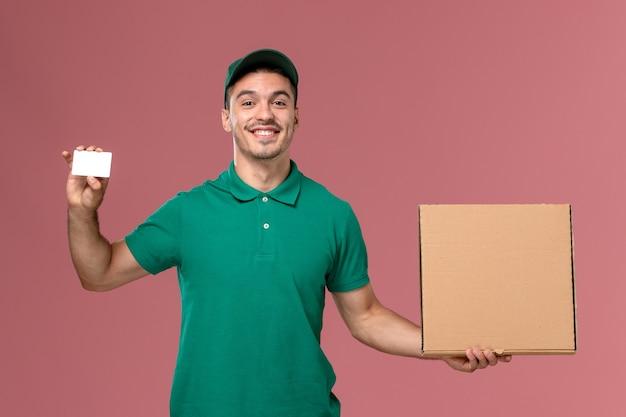 Vooraanzicht mannelijke koerier in groene uniforme voedsel doos met witte kaart op de roze achtergrond te houden