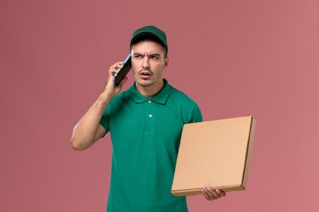 Vooraanzicht mannelijke koerier in groene uniforme voedseldoos houden en met behulp van zijn telefoon op het roze bureau