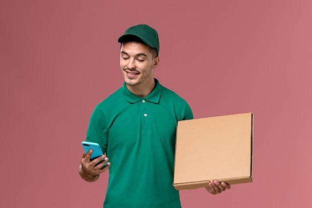 Vooraanzicht mannelijke koerier in groene uniforme voedseldoos houden en telefoon gebruiken op de roze achtergrond