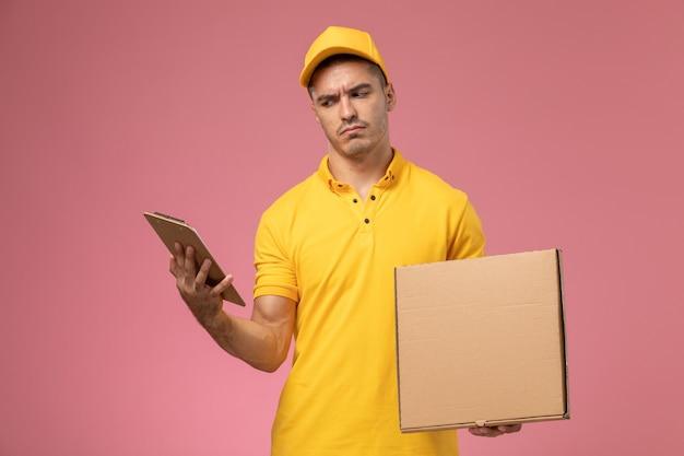 Vooraanzicht mannelijke koerier in het gele eenvormige blocnote van de holdingslezing en de doos van de voedsellevering op de roze achtergrond