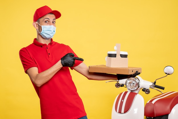 Vooraanzicht mannelijke koerier in masker met bezorgkoffie en doos op de gele dienst covid pandemie kleur virus werk uniform