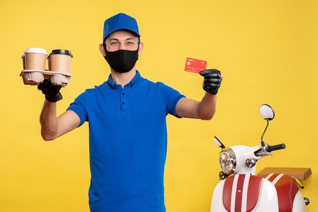 Vooraanzicht mannelijke koerier in masker met koffie en bankkaart op gele werk uniforme covid-levering pandemie baan service