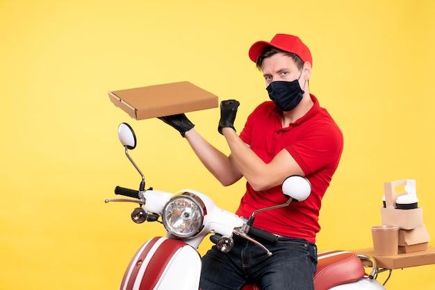 Vooraanzicht mannelijke koerier in masker met voedseldoos op het geel