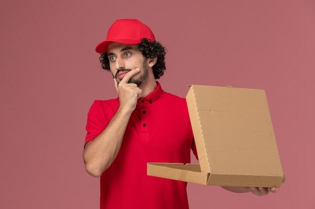 Vooraanzicht mannelijke koerier in rood overhemd en cape die lege doos van het leveringsvoedsel houden die aan de roze muur denken