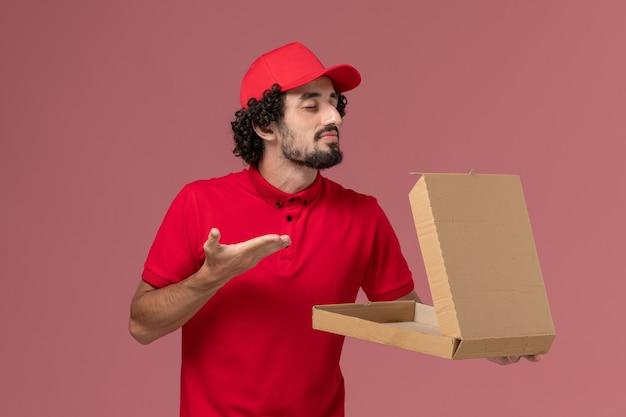 Vooraanzicht mannelijke koerier in rood overhemd en cape die lege doos van het leveringsvoedsel houden die aan de roze muur ruikt