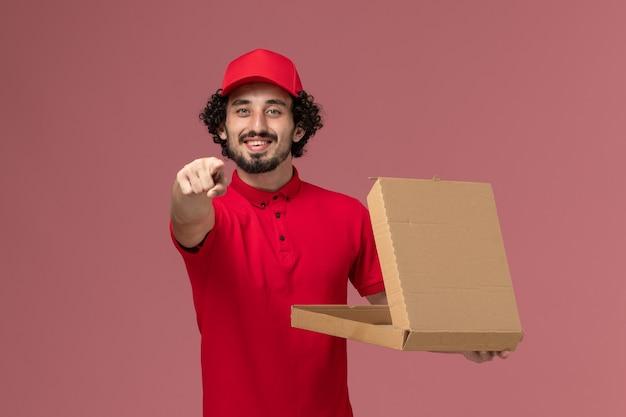 Vooraanzicht mannelijke koerier in rood overhemd en cape die lege doos van het leveringsvoedsel houden en op de roze muur glimlachen