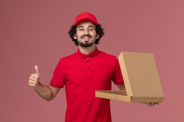 Vooraanzicht mannelijke koerier in rood overhemd en cape die lege doos van het leveringsvoedsel houden en op roze muur glimlachen