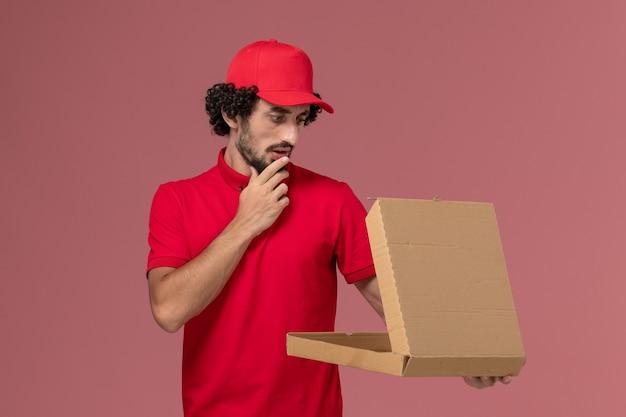 Vooraanzicht mannelijke koerier in rood overhemd en cape die lege doos van het leveringsvoedsel op de lichtroze muur houden