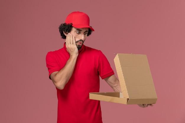 Vooraanzicht mannelijke koerier in rood overhemd en cape die lege doos van het leveringsvoedsel op de roze muur houden