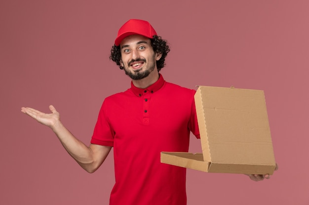 Vooraanzicht mannelijke koerier in rood overhemd en cape die lege leveringsvoedseldoos houden die op de lichtroze muur glimlachen