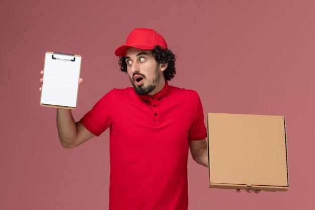 Vooraanzicht mannelijke koerier in rood overhemd en cape die voedseldoos en blocnote op de roze muur houden