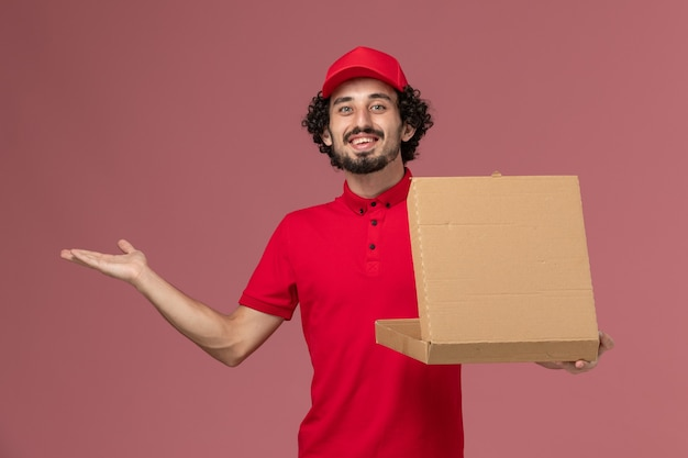 Vooraanzicht mannelijke koerier in rood overhemd en cape die voedseldoos op roze muur houden