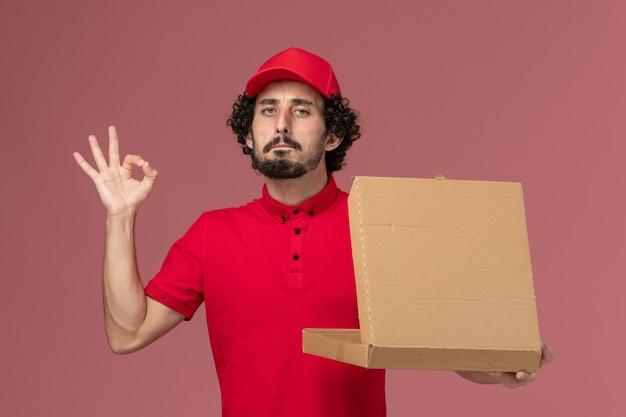 Vooraanzicht mannelijke koerier in rood overhemd en cape met bezorgvoedselbox op de lichtroze medewerker van het bureau-bezorgbedrijf