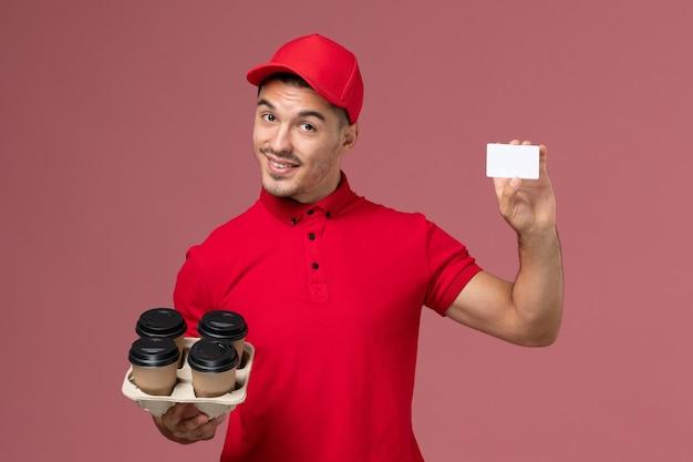 Vooraanzicht mannelijke koerier in rood uniform bezorgen koffiekopjes met witte kaart op de roze muur service levering baan werknemer uniform