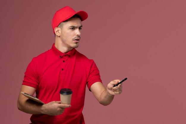 Vooraanzicht mannelijke koerier in rood uniform de koffiekop en blocnote van de holdingslevering op roze muurwerk