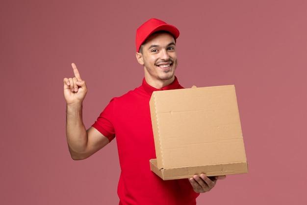 Vooraanzicht mannelijke koerier in rood uniform en cape die voedseldoos vasthoudt en opent glimlachend op lichtroze muurarbeiderbaan