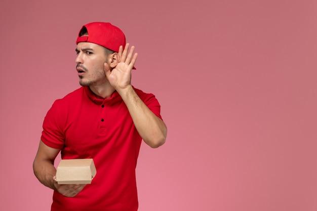 Vooraanzicht mannelijke koerier in rood uniform en cape die weinig leveringspakket houdt dat op roze bureau probeert te horen.