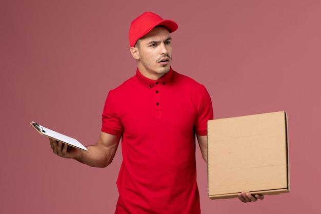 Vooraanzicht mannelijke koerier in rood uniform en cape met blocnote voedseldoos op roze muur service mannelijke levering uniform