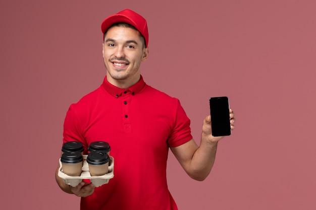 Vooraanzicht mannelijke koerier in rood uniform glimlachend en levering koffiekopjes met telefoon op roze muur te houden