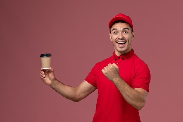 Vooraanzicht mannelijke koerier in rood uniform met bezorging koffiekopje en vreugde op de roze muur mannelijke werknemer