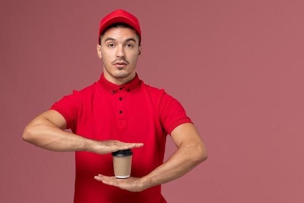 Vooraanzicht mannelijke koerier in rood uniform met bruine levering koffiekopje op roze muur service bezorger mannelijke uniforme baan