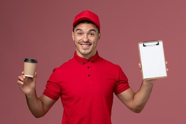 Vooraanzicht mannelijke koerier in rood uniform met koffiekopje en blocnote op het roze mannetje van de muurarbeider