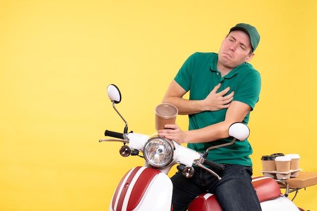 Vooraanzicht mannelijke koerier in uniform met koffiekopje met hartzeer op geel