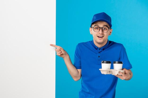 Vooraanzicht mannelijke koerier in uniform met koffiekopjes op blauw