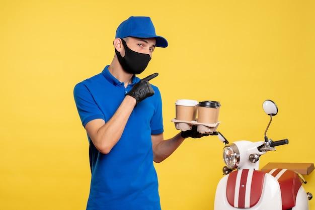 Vooraanzicht mannelijke koerier in zwart masker koffie houden op gele baan covid-pandemische dienst levering uniform werk