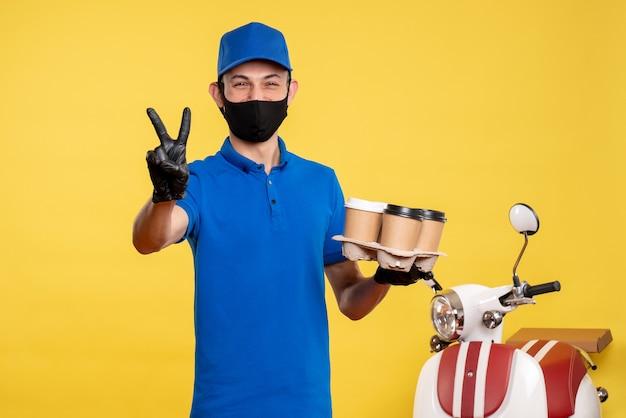 Vooraanzicht mannelijke koerier in zwart masker koffie op gele levering baan covid pandemie werk service uniform te houden